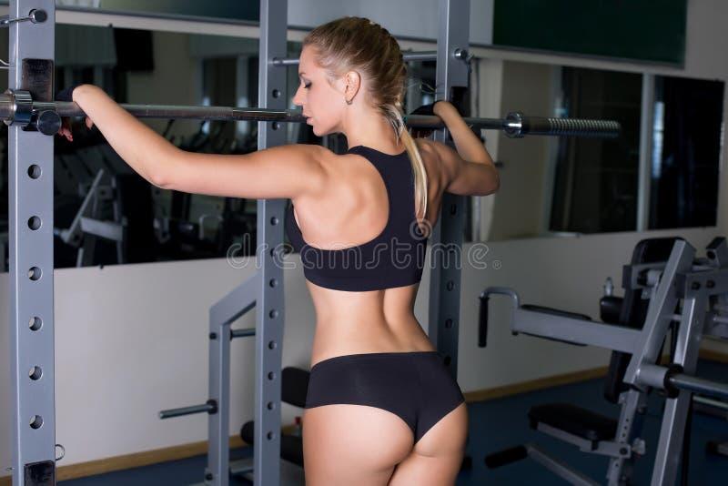Menina com o corpo perfeito que executa o exercício do barbell foto de stock