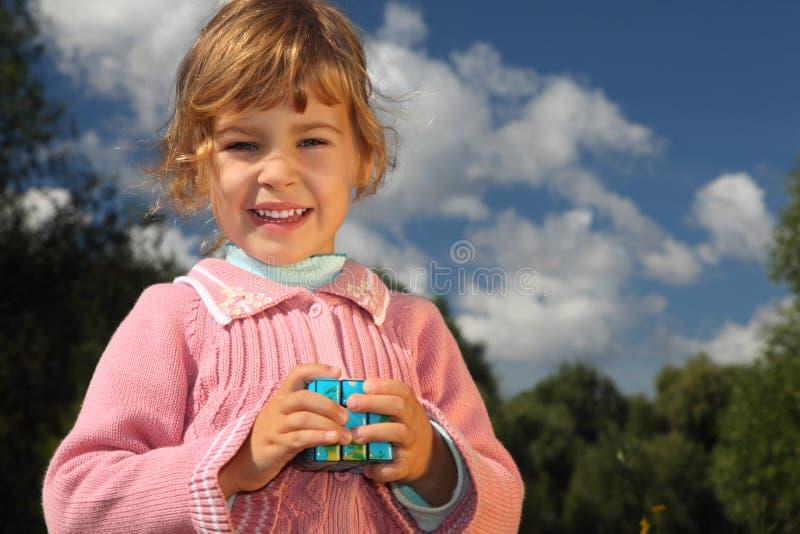 Menina com o cubo mágico ao ar livre foto de stock