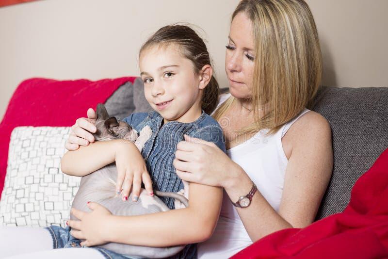 Menina com o gato da mãe no sofe em casa fotos de stock