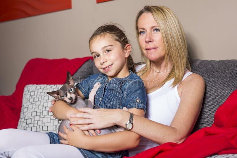 Menina com o gato da mãe no sofe em casa imagens de stock royalty free