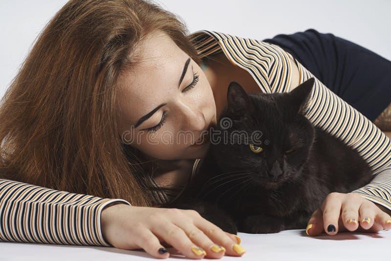 Menina com o gato pernicioso preto no branco quase isolado imagens de stock royalty free