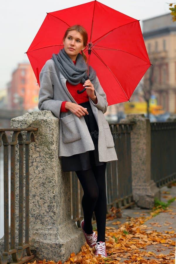Menina com o guarda-chuva vermelho na cidade do outono fotos de stock royalty free
