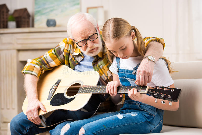 Menina com o homem superior que senta-se no sofá e que joga a guitarra acústica fotos de stock