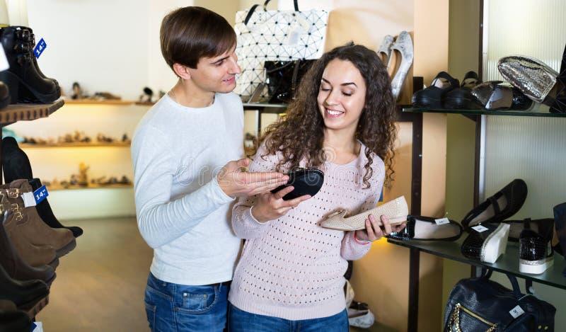 Menina com o indivíduo que escolhe sapatas das mulheres do verão em uma sapataria fotos de stock