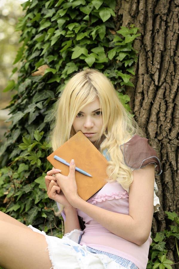 Menina com o livro ao ar livre. imagens de stock