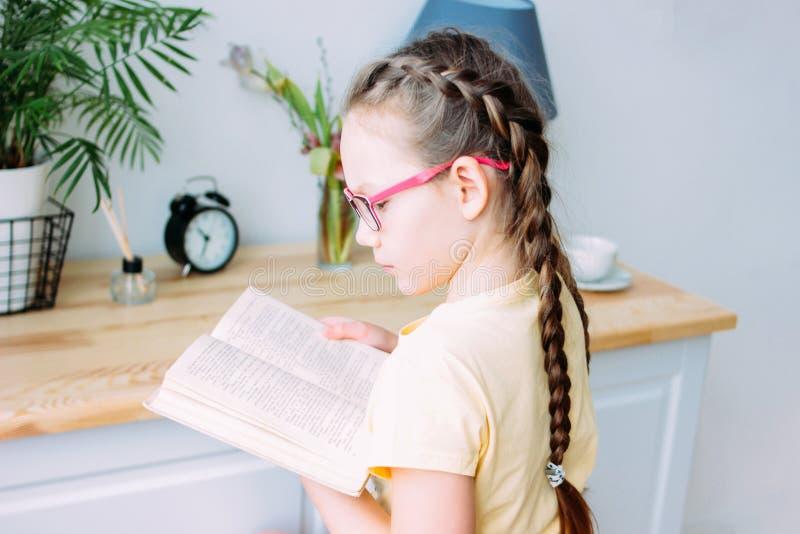 Menina com o livro de leitura dos vidros e das tranças na tabela em sua sala fotografia de stock