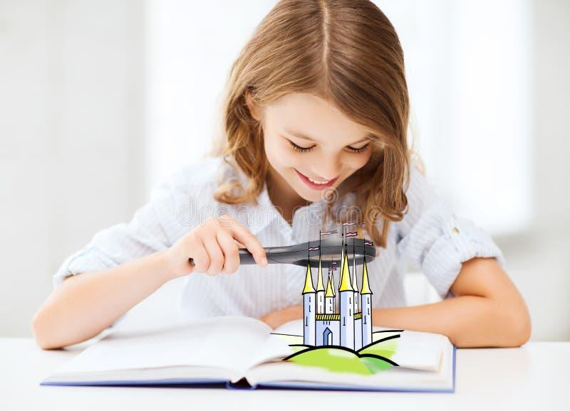Menina com o livro que olha ao castelo através da lente de aumento foto de stock royalty free