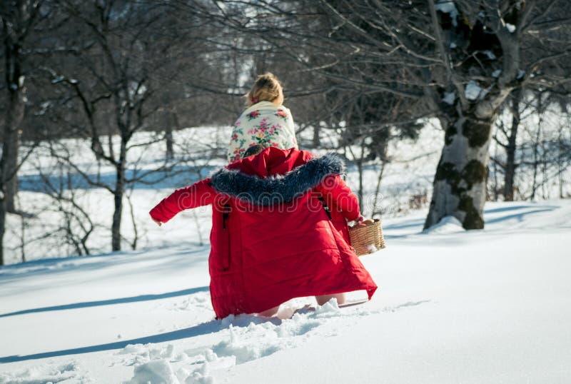 Menina com o mum que anda na neve imagem de stock