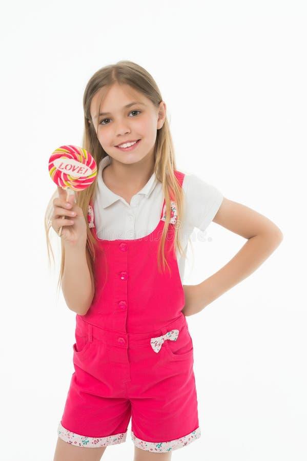Menina com o pirulito do arco-íris isolado no fundo branco Caçoe com cabelo louro longo em macacões cor-de-rosa Apreciação do gul imagem de stock royalty free