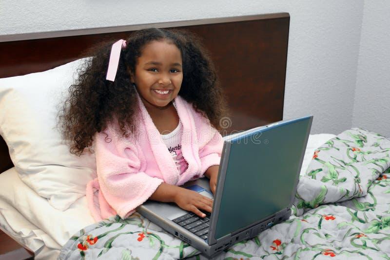 Menina com o portátil na cama fotografia de stock