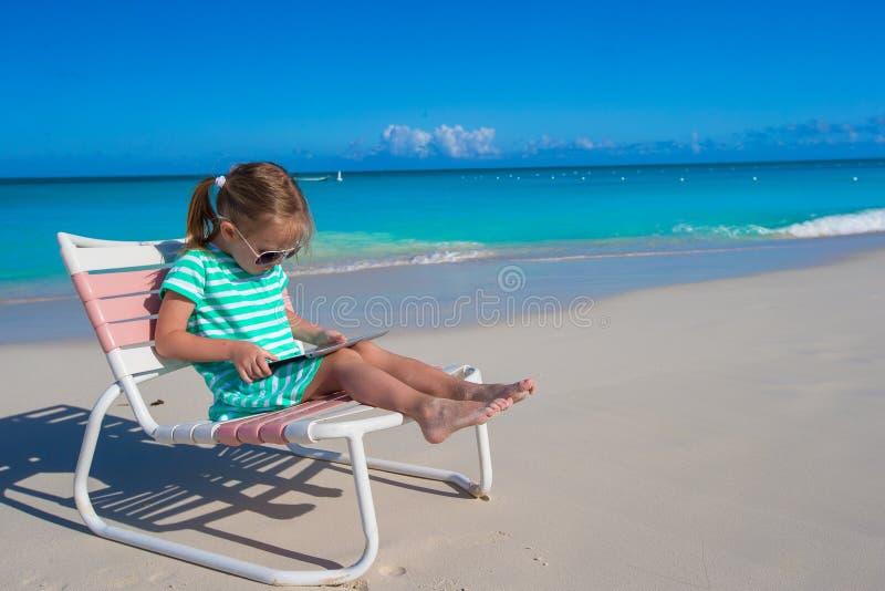 Menina com o portátil na praia durante o verão imagem de stock royalty free