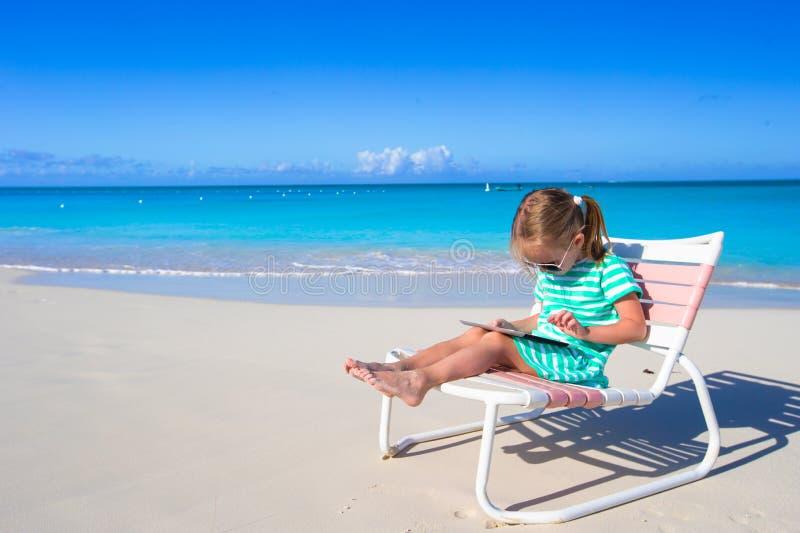 Menina com o portátil na praia durante o verão foto de stock royalty free