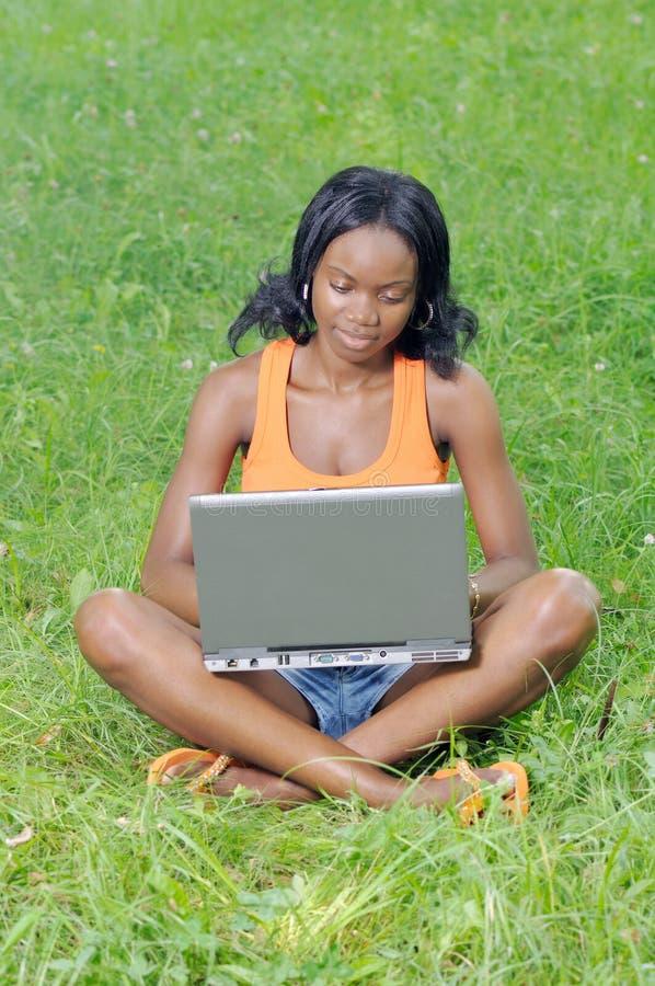 Menina com o portátil no parque foto de stock royalty free