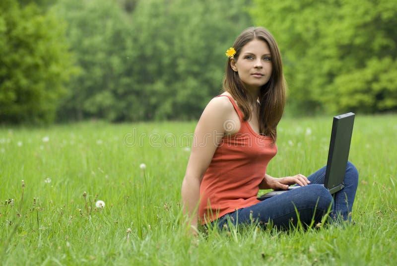 Menina com o portátil que relaxa na grama imagem de stock