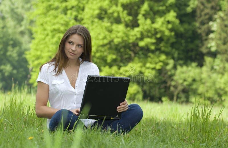 Menina com o portátil que relaxa na grama foto de stock