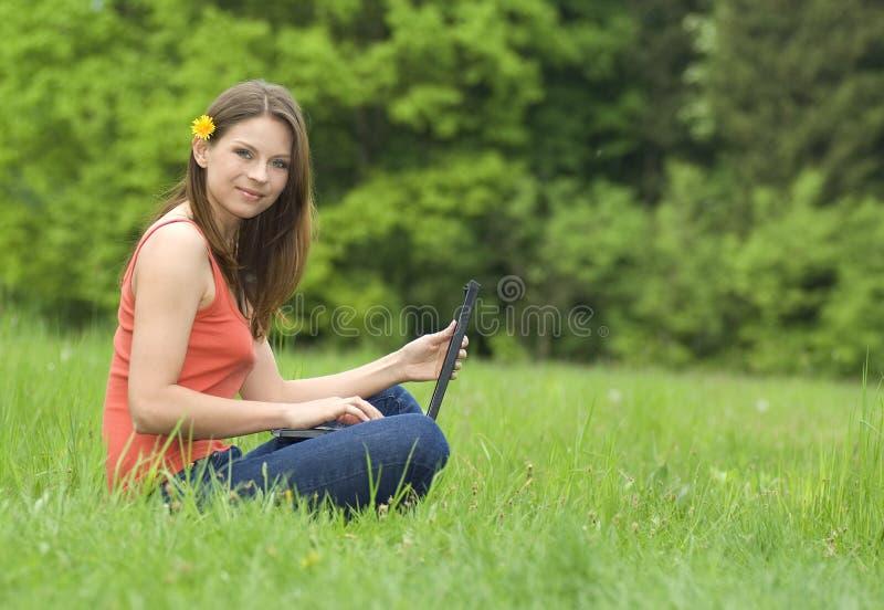 Menina com o portátil que relaxa na grama imagem de stock royalty free