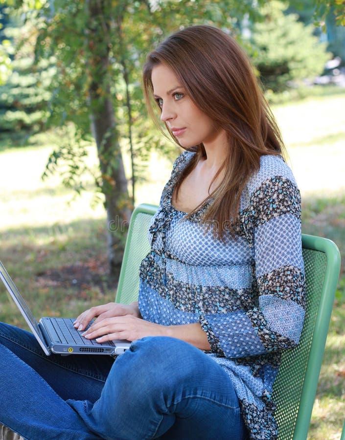 Menina com o portátil que relaxa na grama fotografia de stock