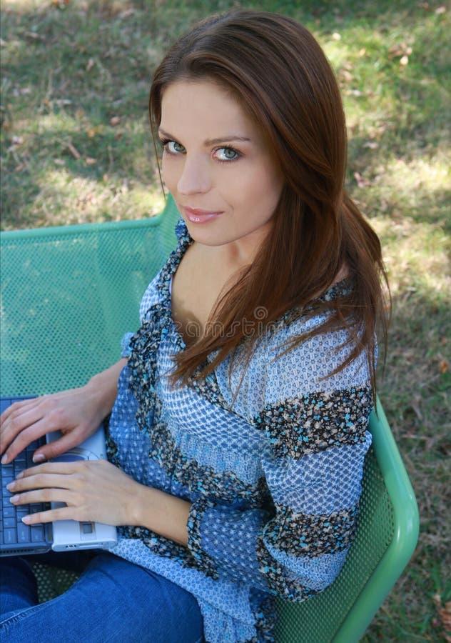 Menina com o portátil que relaxa na grama fotografia de stock royalty free