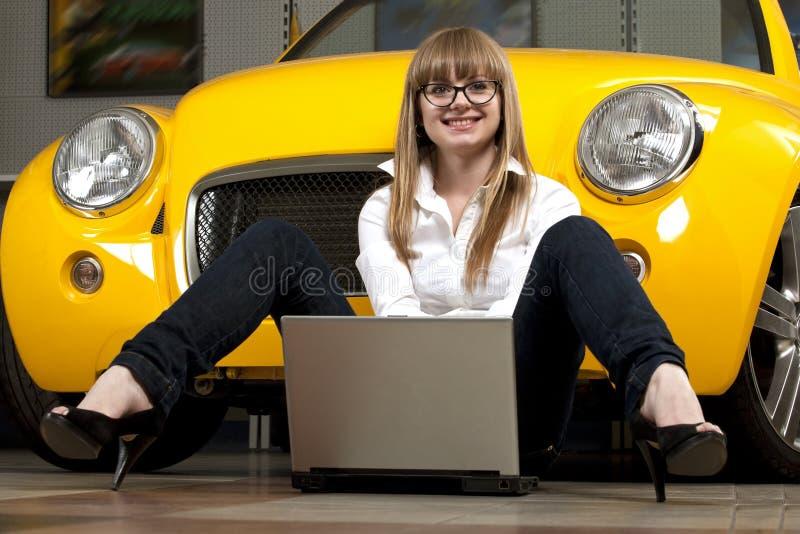 Menina com o portátil que senta-se de encontro do carro amarelo fotos de stock royalty free