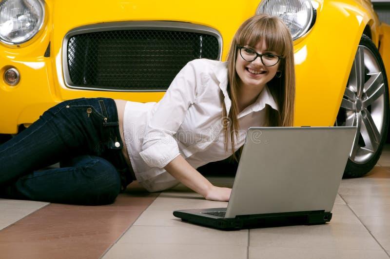 Menina com o portátil que senta-se de encontro do carro amarelo imagem de stock