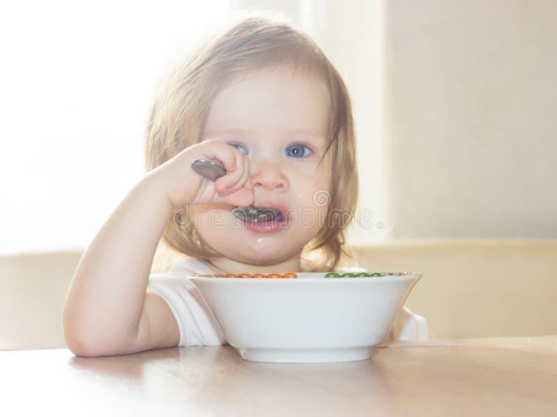 A menina com o prazer sozinho guarda uma colher e come o alimento delicioso de uma placa branca imagem de stock