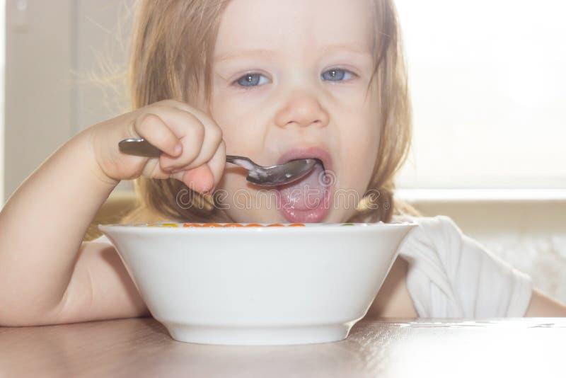 A menina com o prazer sozinho guarda uma colher e come o alimento delicioso de uma placa branca imagens de stock