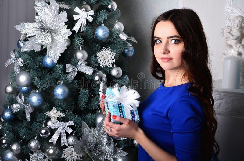 Menina com o presente perto da árvore de Natal fotografia de stock royalty free