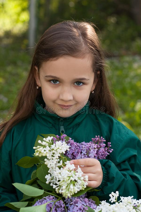Menina com o ramalhete de flores lilás no jardim imagens de stock royalty free