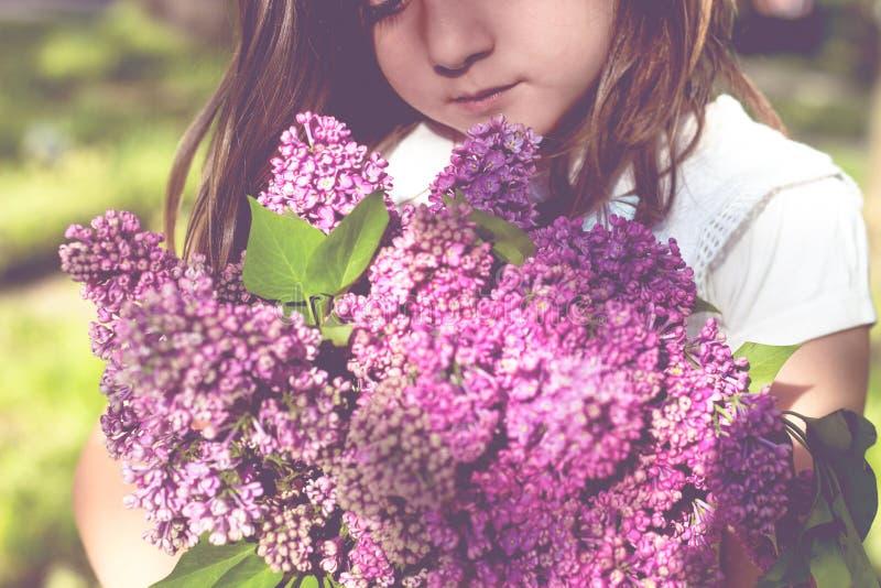 Menina com o ramalhete do lilás em suas mãos imagem de stock royalty free