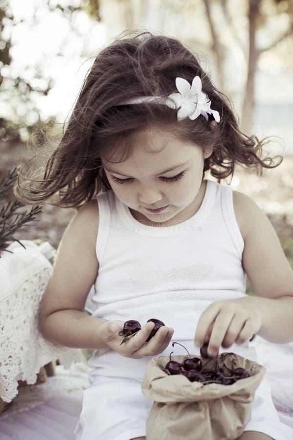 Menina com o saco de cerejas maduras imagem de stock royalty free