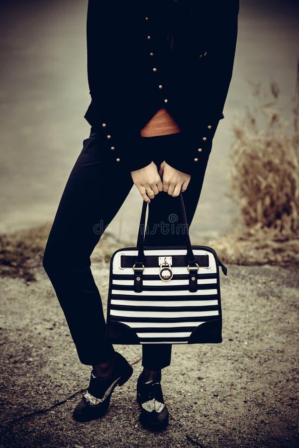 Menina com o saco preto e branco nas mãos foto de stock