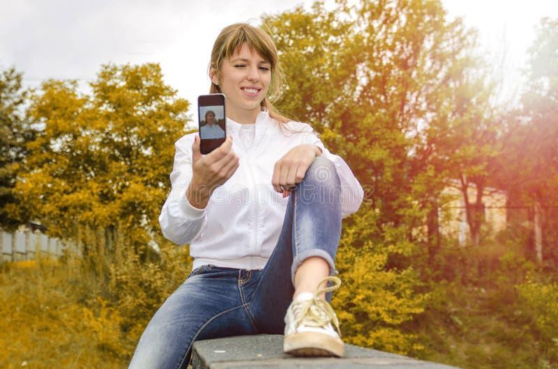 A menina com o telefone no parque faz o selfie imagens de stock
