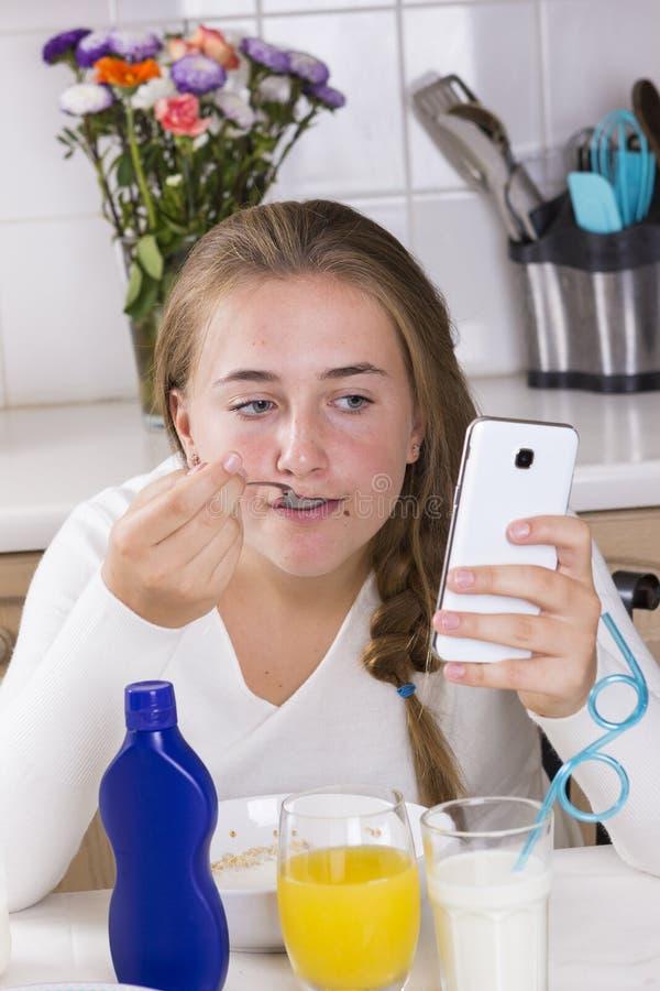 Menina com o telefone que come o café da manhã na cozinha fotografia de stock royalty free