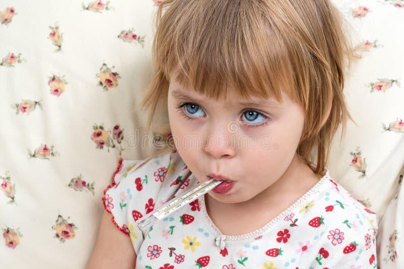 Menina com o termômetro na boca fotografia de stock royalty free