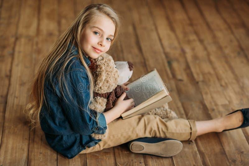 A menina com o urso de peluche que guarda o livro, educação caçoa o conceito imagens de stock