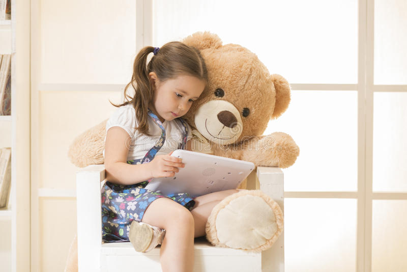 Menina com o urso de peluche que olha seu tablet pc fotos de stock royalty free