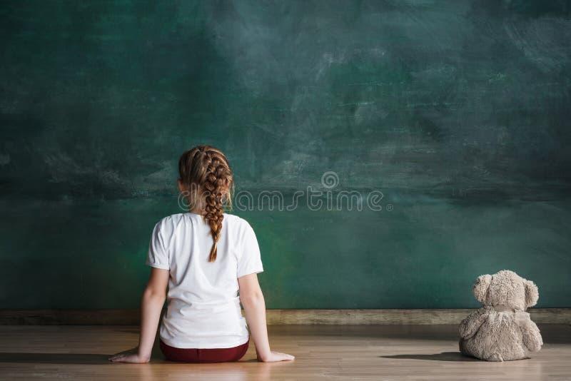 Menina com o urso de peluche que senta-se no assoalho na sala vazia Conceito do autismo foto de stock royalty free
