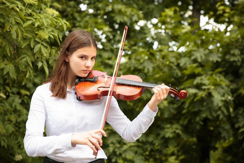 Menina com o violino ao ar livre fotografia de stock