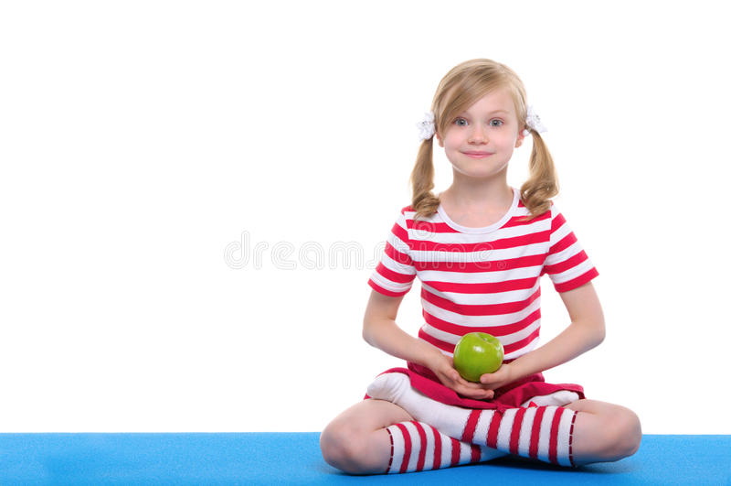 A menina com olhos abertos pratica a ioga e mantem a maçã foto de stock royalty free