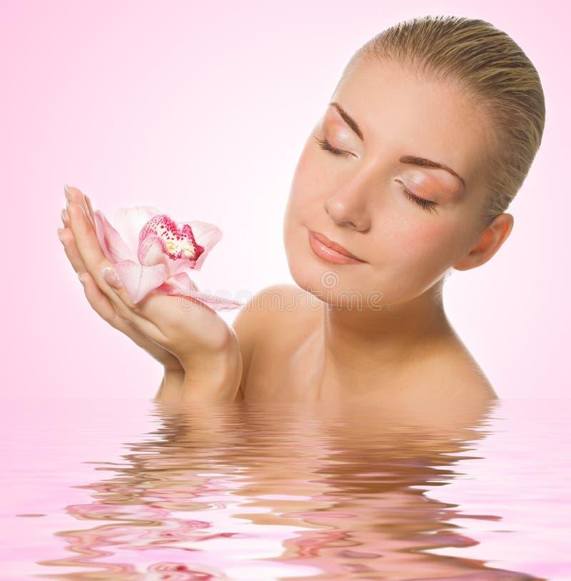 Menina com orquídea cor-de-rosa imagem de stock