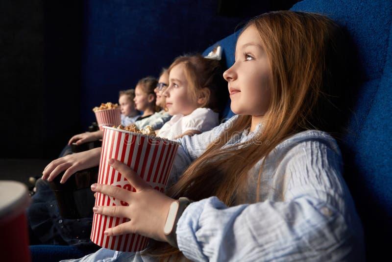 Menina com os amigos que sentam-se no cinema fotos de stock royalty free