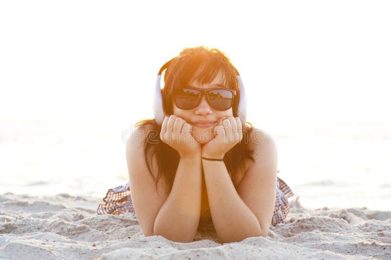 Menina com os auscultadores na areia da praia. imagem de stock royalty free