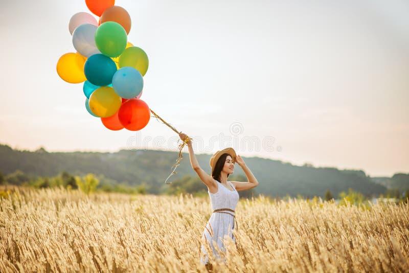 Menina com os balões de ar coloridos em um campo do centeio foto de stock