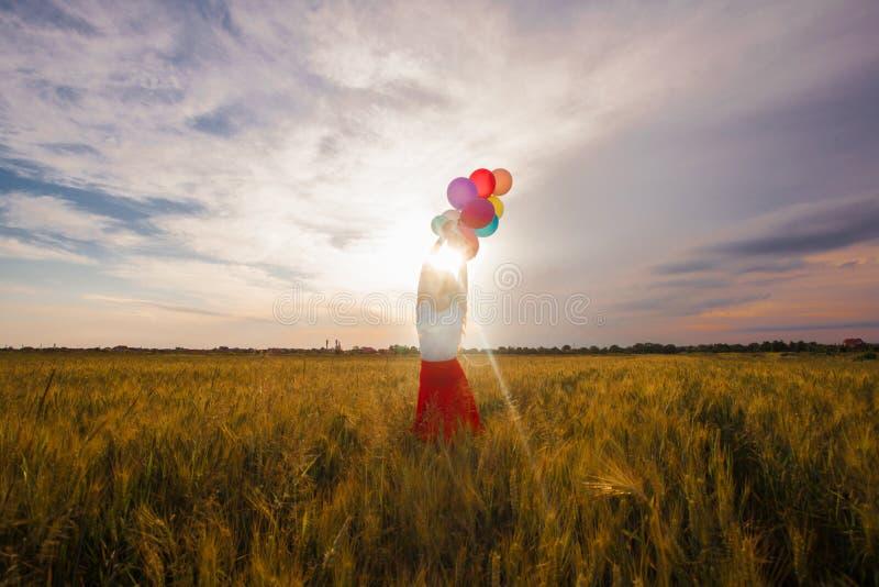 Menina com os balões no campo de trigo foto de stock royalty free