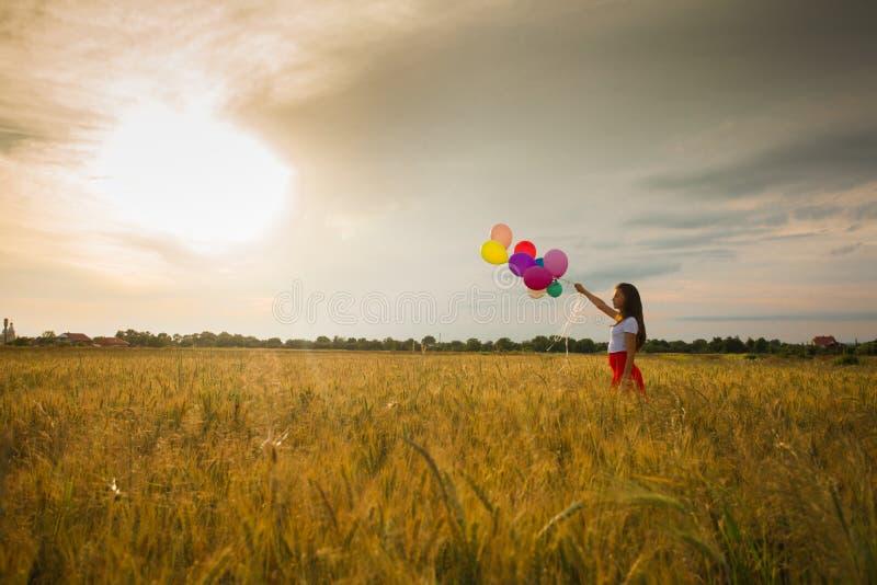 Menina com os balões no campo de trigo fotos de stock