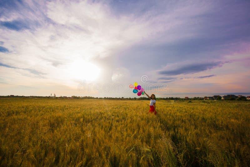 Menina com os balões no campo de trigo imagens de stock