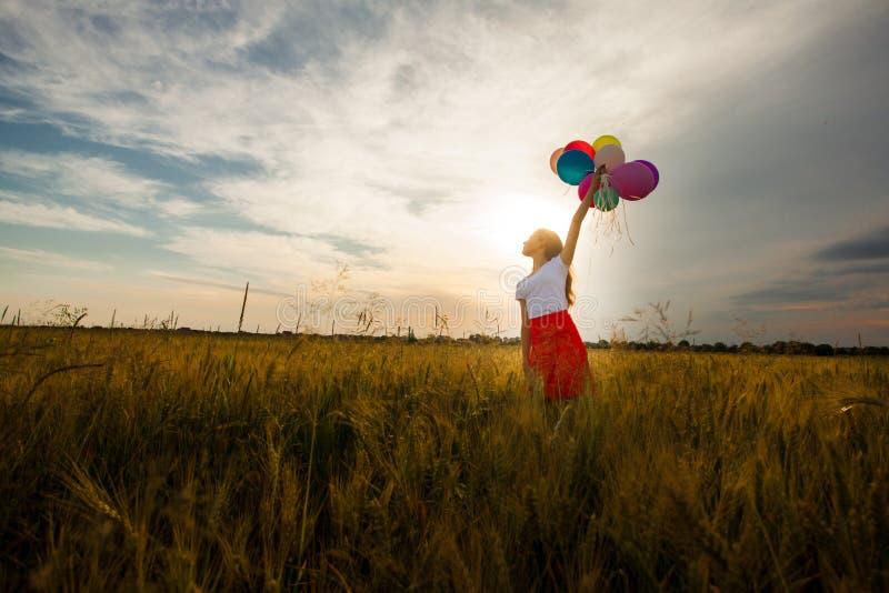 Menina com os balões no campo de trigo fotografia de stock