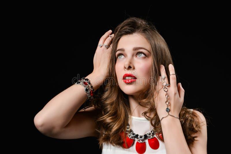 menina com os bordos brilhantes no estúdio Bijutaria da joia - brincos, bracelete, colar vermelha Forma, beleza, joia fotografia de stock