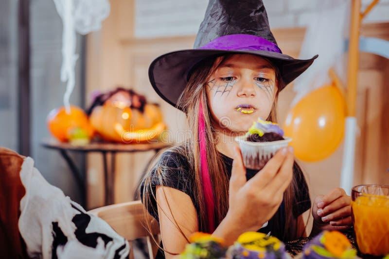 A menina com os bordos roxos e amarelos que vestem Dia das Bruxas sere comer o queque brilhante fotos de stock royalty free