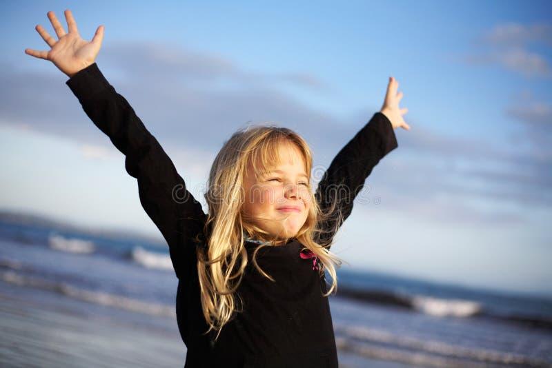 Menina com os braços outstretched na praia fotos de stock royalty free